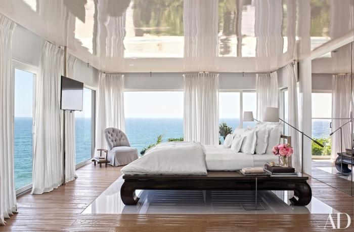 habitaciones modernas, habitación espaciosa con grandes ventanales y cortinas en blanco, cama de madera con patas vintage, vista al mar