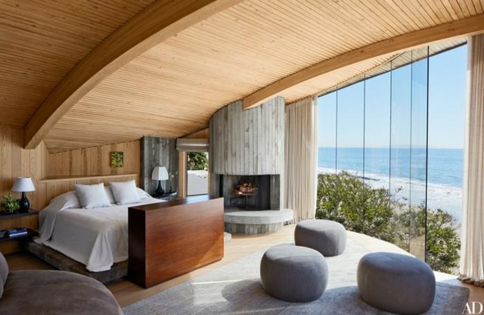 dormitorios de matrimonio, grande habitación con interesantes elementos, techo de madera, inclinado, chimenea de leña y grandes ventanales con vista al mar