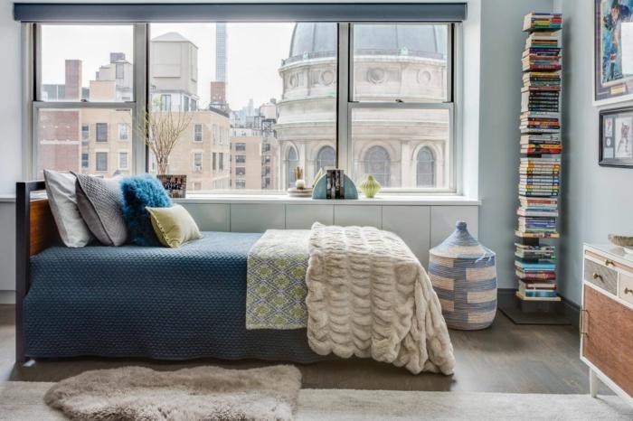 dormitorios de matrimonio, bonita habitación con vista, cobijas decorativas y muchos libros colocados en fila, suelo de parquet