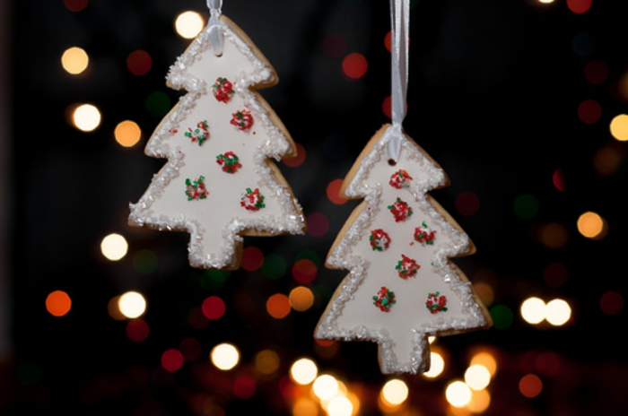 como hacer galletas de navidad, árboles blancos decorados con glaseado real, palitos de azúcar en rojo, verde y blanco