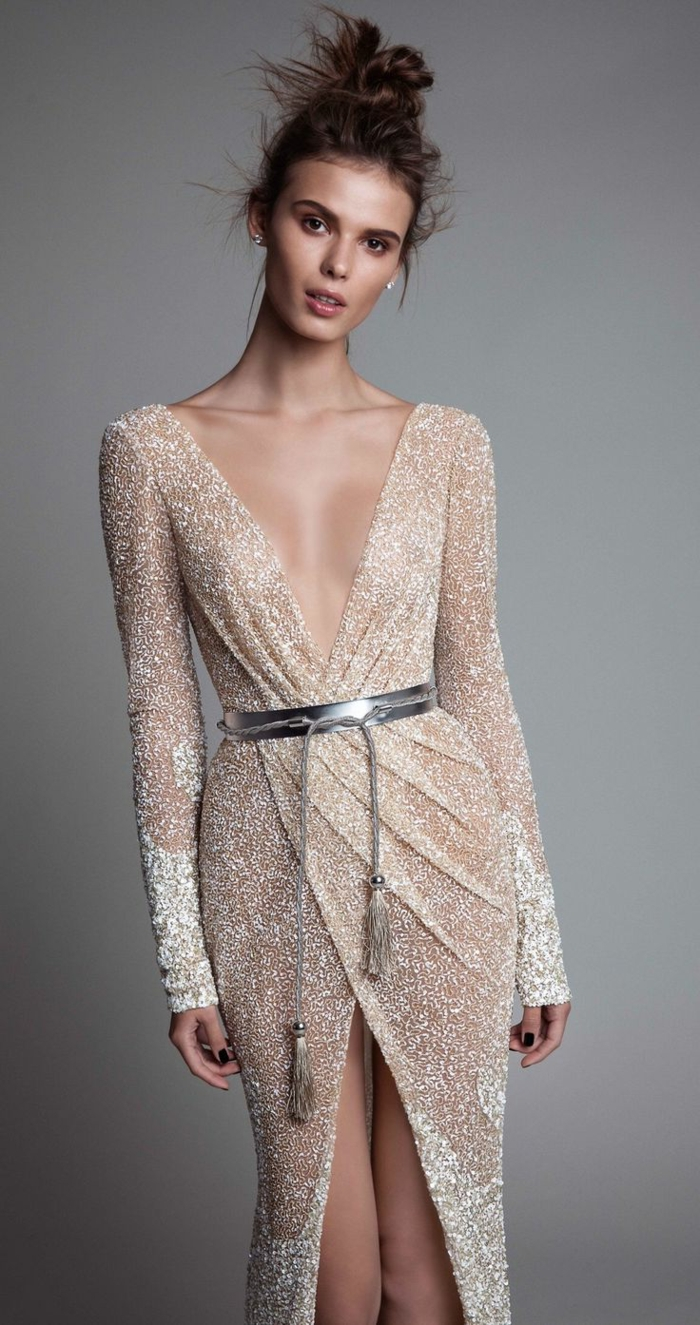 vestidos nochevieja, vestido largo de color champán con partículas relucientes y detalle en color plata, escote muy atrevido, peinado interesante en moño