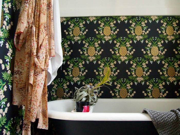 muebles de baño, baño en estilo bohemio con papel pintada con piñas en fondo negro, bañera moderna y decoración de flores