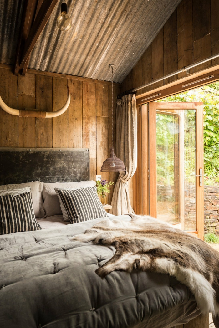 casa de madera, precioso dormitorio en estilo rústico, cama de madera con cabecero, cobijas de piel