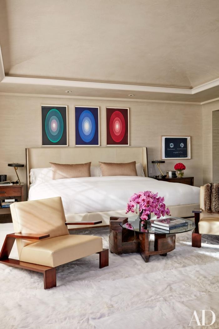 dormitorios de matrimonio, elegante habitación en beige con decoración en la pared, alfombra peluda en blanco y sillones modernos tapizados de piel