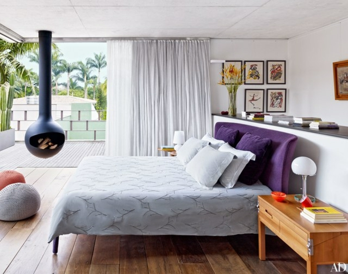 dormitorios de matrimonio, ideas de decoración de dormitorios 2018, cama tapizada de terciopelo en color lila, chimenea de leña colgante, suelo de madera