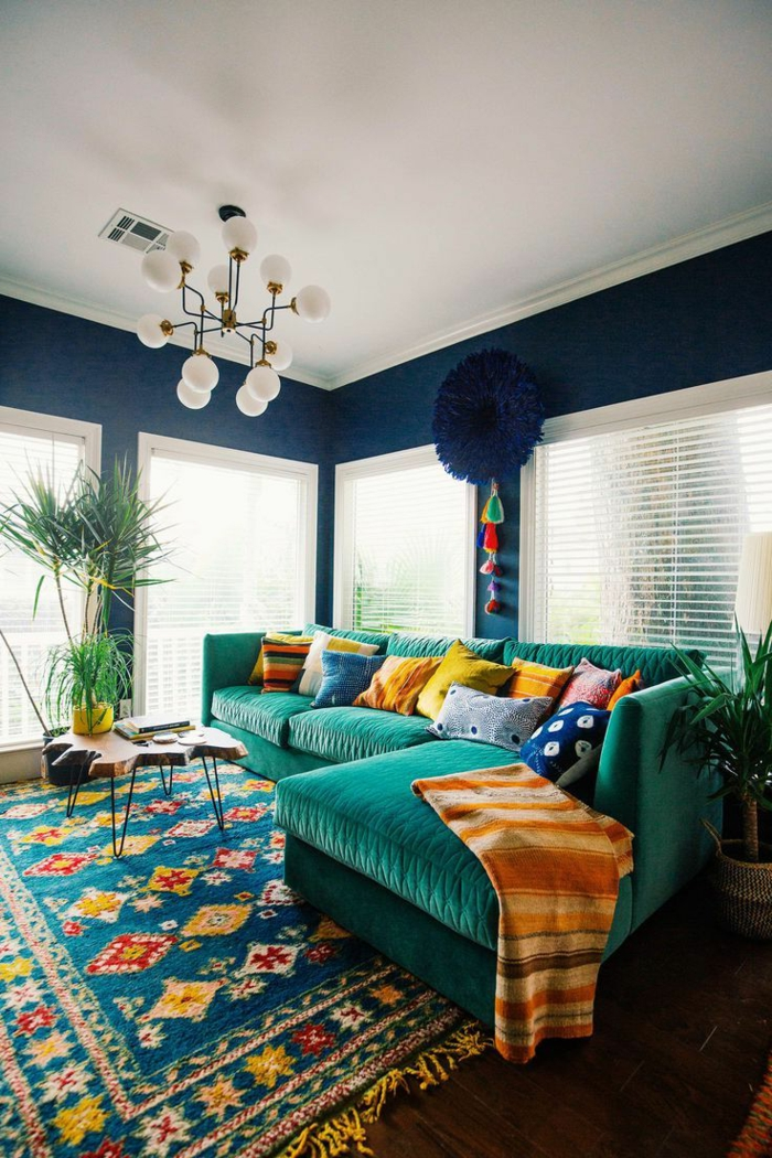 muebles de salon, salón moderno en colores saturados, alfombra vintage, sofá tapizada en terciopelo verde, lámpara de araña blanca