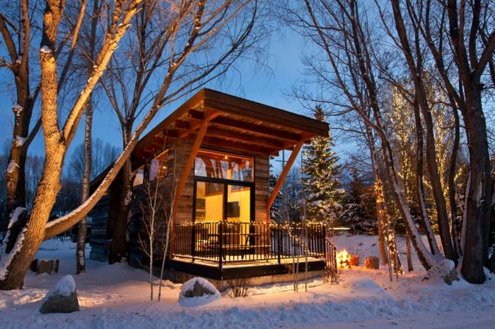 casa de madera, casa de diseño moderno con pequeña veranda decorada de bombillas, árboles con decoración de navidad