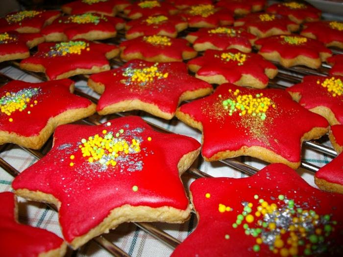 galletas de mantequilla receta, estrellas de navidad decoradas en rojo con bolitas de azúcar en amarillo y verde