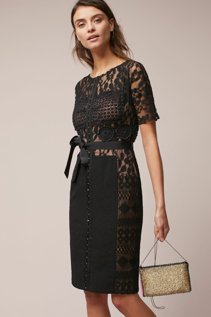 vestidos de fiesta largos, vestido negro con partes transparentes y elementos de encaje, cinturón de satén, pequeño bolso brillante en color oro
