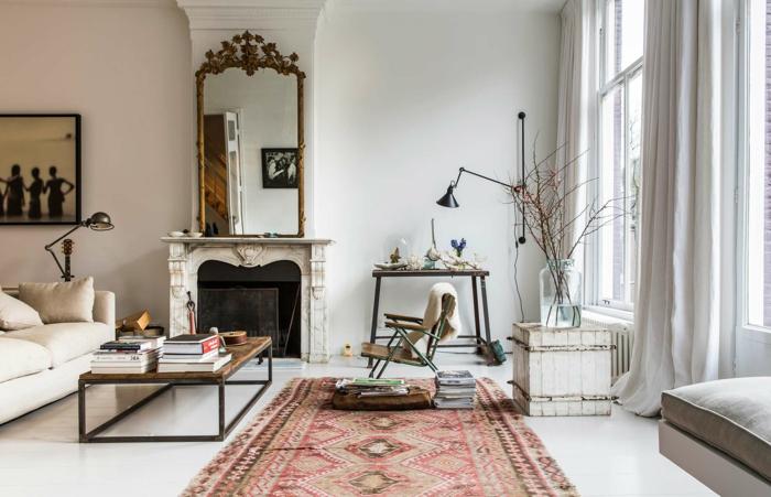 salon, ambiente en blanco con alfombra en colores cálidos, espejo vintage y chimenea de leña