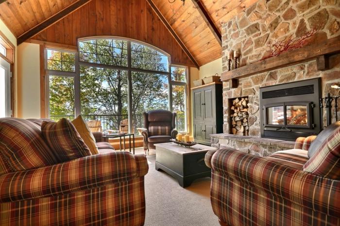 cabañitas del bosque, salón acogedor en tonos terrosos, sillones con estampado de cuadrados, techo con vigas de madera y chimenea de leña