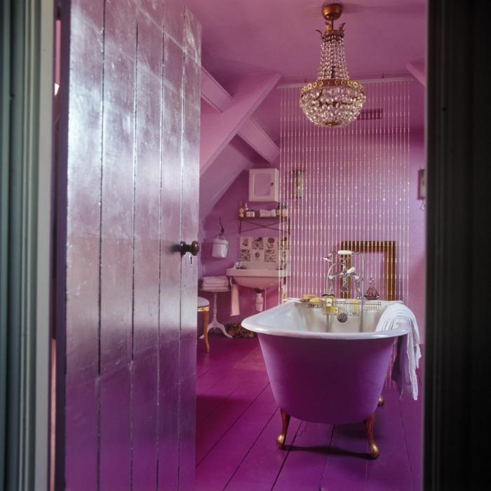 muebles de baño, idea extravagante en color lila saturado, puerta y suelo de madera, lámpara de araña con ornamentos de cristal, bañera patas garra
