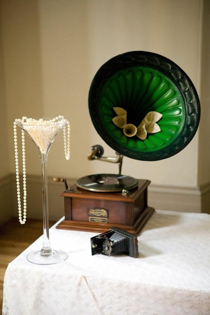 decoracion vintage, gramófono vintage en verde, decoración de collar de perlas puesto en vaso de cristal alto, paredes en beige