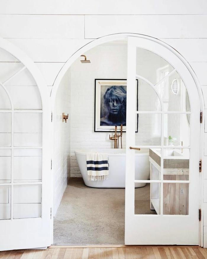 cuadros baratos, puerta de arco, baño blanco, bañera grande, cuadro con retrato de mujer en azul, marco negro