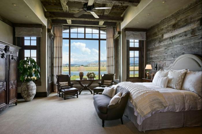 cabañas de madera, dormitorio de encanto con vista, muebles vintage en color marrón, cama con cabecero en beige, paredes con vigas de madera