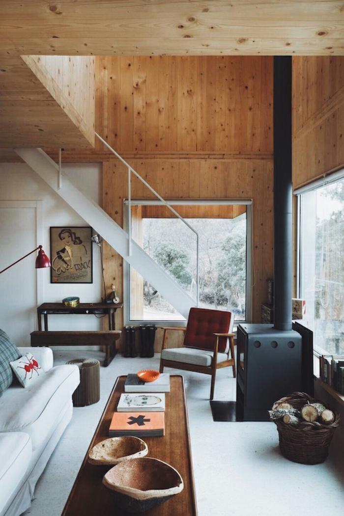 cabañas de madera, salón de maravilla en una casa de campo, paredes y techo con vigas de madera, mesa larga de madera y sofá tapizada en blanco