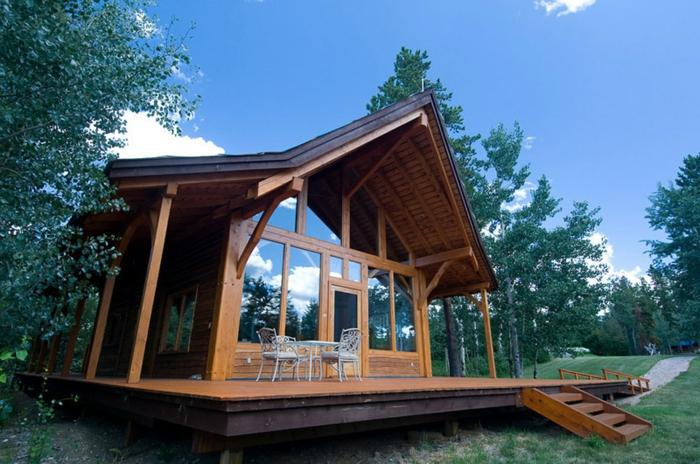 cabañas de madera, propuesta de cabaña de madera moderna hecha de madera con ventanales, veranda con mesa y sillas