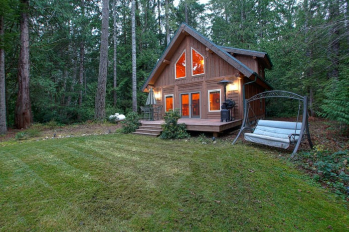 cabañas de madera, prado en el bosque con pequeña cabaña de madera con veranda y escaleras, columpio al lado de la casa