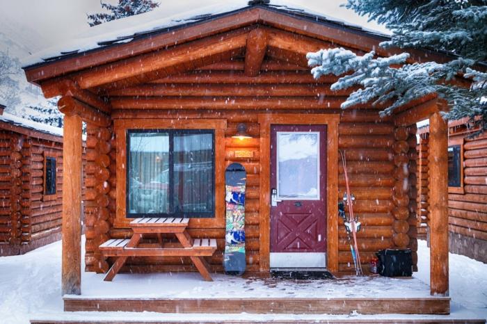 cabañas rurales, propuesta acogedora, cabaña pequeña hecha de leña, banco con mesa en la veranda, paisaje invernal