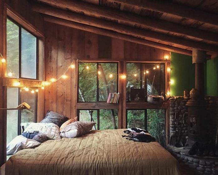 cabañas rurales, dormitorio de encanto con bombillas decorativas, estufa de hierro, paredes con vigas de madera