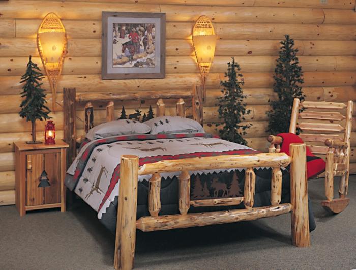 cabañas rurales, dormitorio acogedor con cama hecha de leña, cobijas con motivos invernales, pinos decorativos