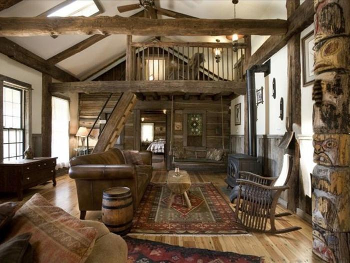 cabañas rurales, grande salón decorado en estilo rústico, escaleras de madera, alfombras y cojines con motivos geométricos, vigas de madera en la pared