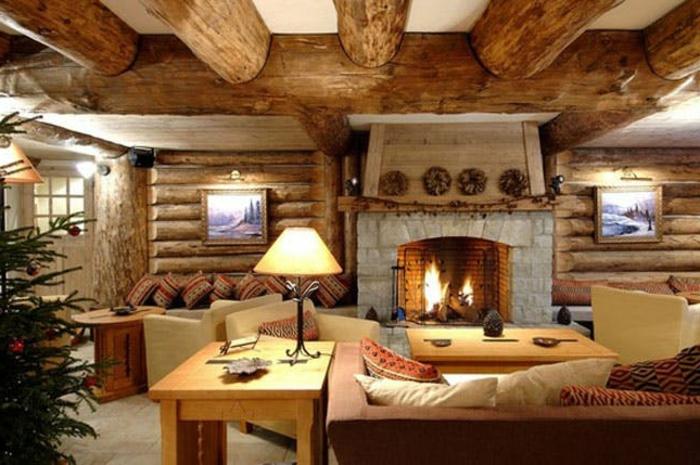 cabañas rurales, interior de encanto decorado en estilo rústico, grande chimenea de piedra, mesas de madera, techo con grandes vigas de madera