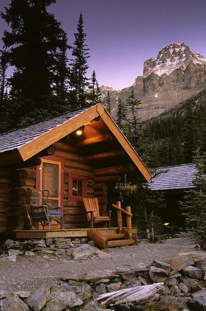 cabañas rurales, pequeña cabañita hecha de madera colocada en un bosque en la montaña, terreno de piedra, pequeña veranda
