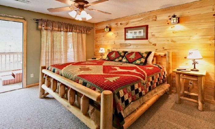 cabañas rurales, dormitorio en colores cálidos con muebles y paredes de madera, suelo de moqueta, cobijas con motivos invernales
