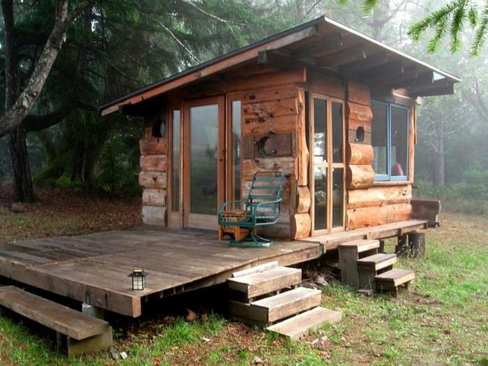 casitas de madera, cabaña de madera con veranda, pequeña casa de madera con ventanales colocada en el bosque