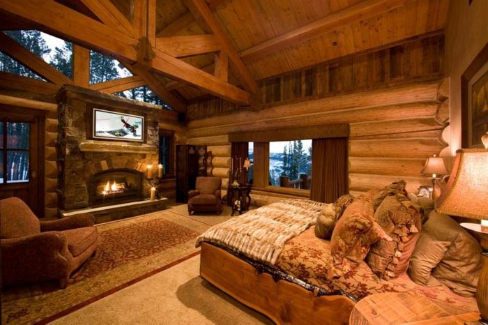 cabañas con encanto, dormitorio acogedor en colores calientes techo con vigas de madera, cama doble con muchas almohadas y cojines decorativos