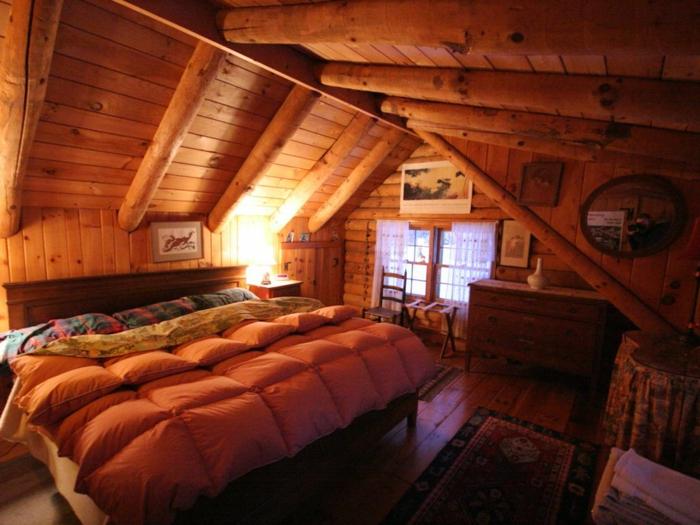 cabañas con encanto, habitación acogedora colocada en la buhardilla, techo inclinado con vigas de madera, cama doble hecha de madera