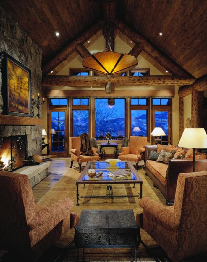 cabañas con encanto, grande salón estilo rústico colocado en la buhardilla, chimenea de leña y lámparas empotradas en el techo