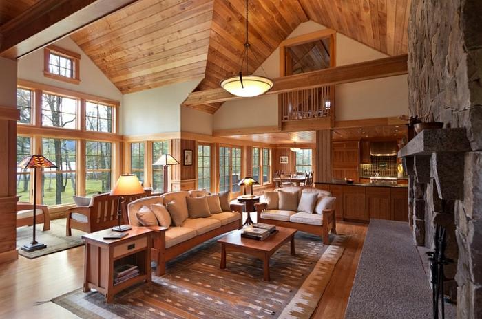 cabaña de madera, interior en estilo rústico, grande salón con techo alto tapizado de madera, ventanales de madera con vista