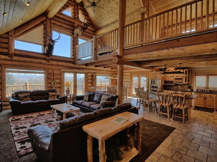 cabañas con encanto, interior en estilo rústico, casa de madera de dos plantas, sofás de piel, techo inclinado con lámparas empotradas