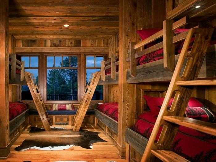 cabaña de madera, interior de cabaña, habitación hecha de madera con muchas camas en dos plantas y lamparas empotradas