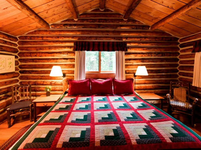 cabaña de madera, habitación acogedora, cama doble con cobija de lana, paredes y techo de madera, cojines decorativos en rojo