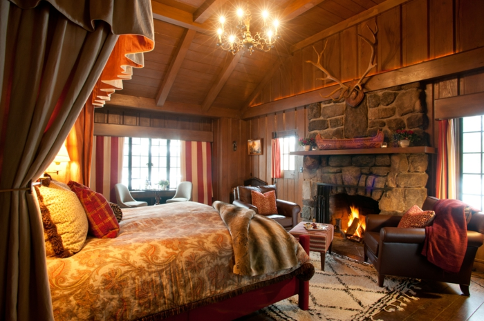 cabañas con encanto, habitación en colores cálidos, grande chimenea de leña, techo y paredes de madera