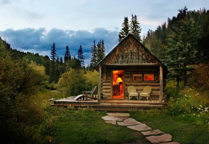 cabaña de madera, cabaña rural hecha de madera, veranda con sillas, sendero de piedras, prado en el bosque