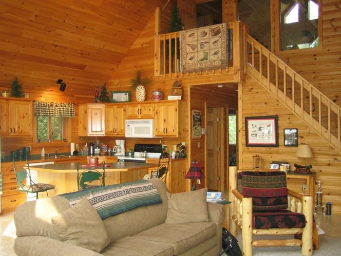 cabaña de madera, interior con vigas de madera, cabaña en dos plantas con techo inclinado, sofá cómoda en beige