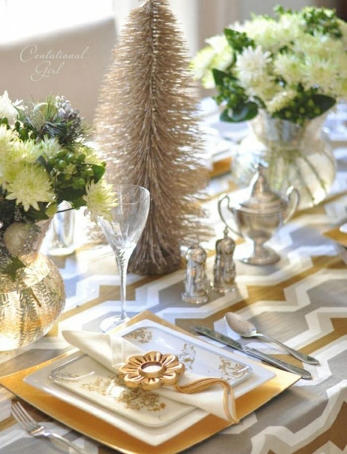 centro de mesa, decoracion con ornamentos navideños dorados y jarrones de vidrio con ramos de flores blancos