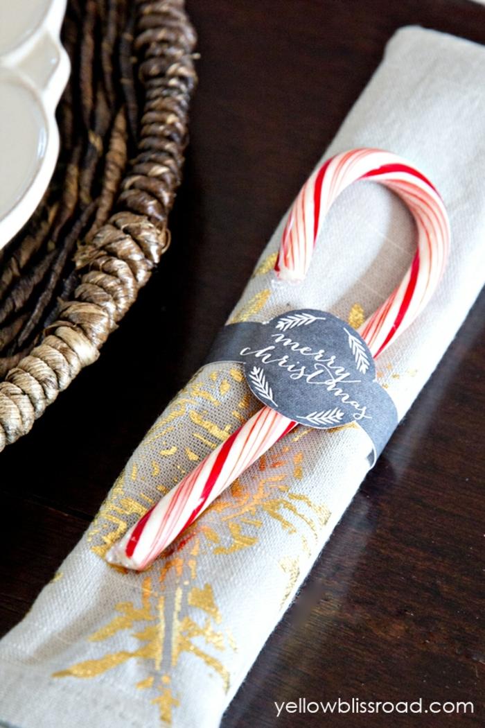 centro de mesa, elemento atractivo para decorar la mesa de navidad, servilleta en beige con una piruleta en blanco y rojo