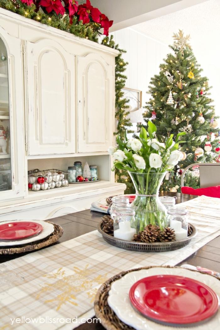 centros navideños. comedor estiloso en colores claros, centro de mesa de flores y piñas, platos en rojo