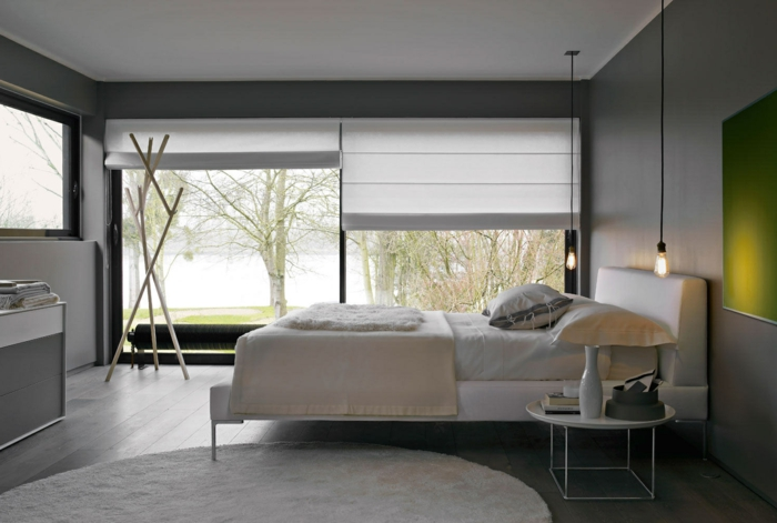dormitorio matrimonio, bonita habitación en blanco y gris con detalle en verde, alfombra oval en blanco, suelo de madera