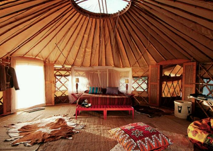 muebles salon, salón colocado en la buhardilla, decoración en estilo bohemio, cama doble y banco pie de cama rojo
