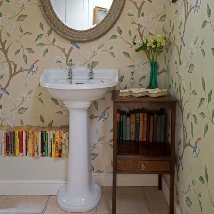 baños modernos, baño ecléctico con estantería de libros, armario vintage de madera y papel pintado con estampado de flores