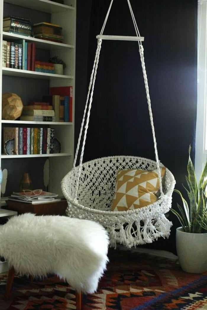 muebles salon, silla blanca colgada en el techo, estantes con libros, interior en estilo boho chic