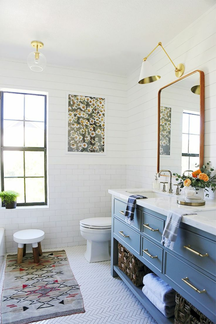 baños modernos, baño grande con ventana y mucha luz, mueble azul, espejo grande y tapete, ladrillo visto blanco, foto de margaritas laminada