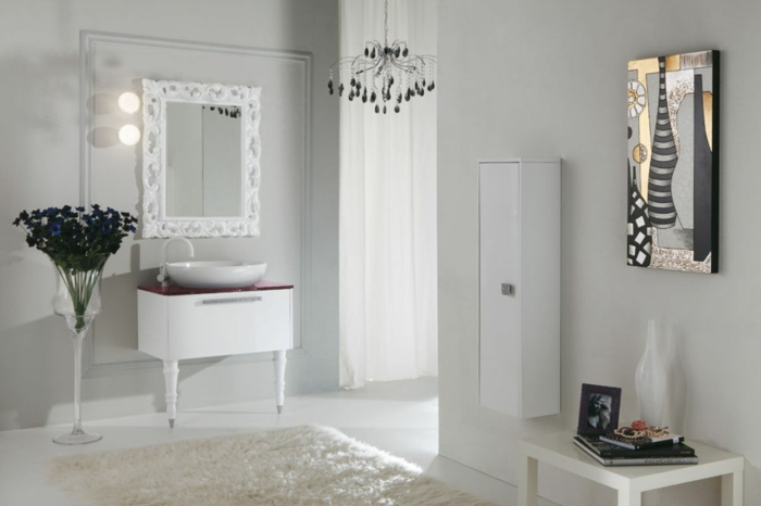 baños modernos, baño con alfombra, todo blanco. lámpara de araña, pintura nature morte como acento, espejo con marco grande
