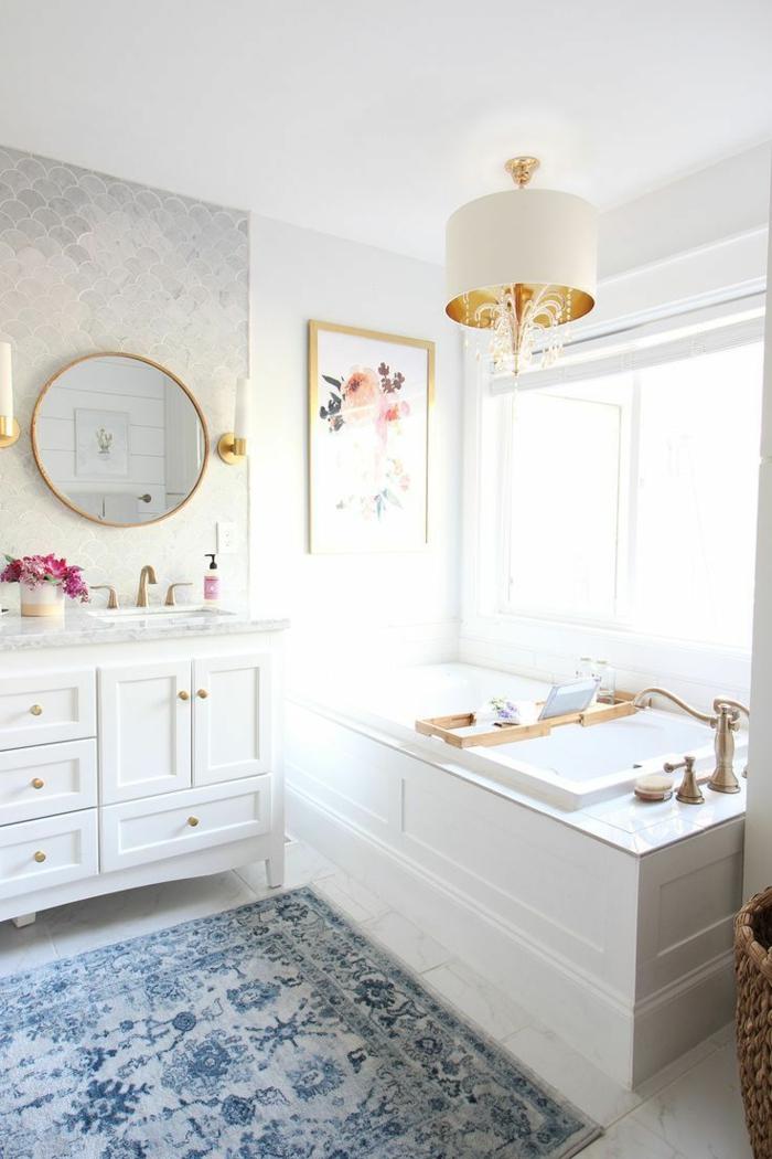 laminas vintage, baño de lujo con alfombra azul, muebles blancos con acentos en dorado, ventana grande, lamina con flores de colores sobre la bañera